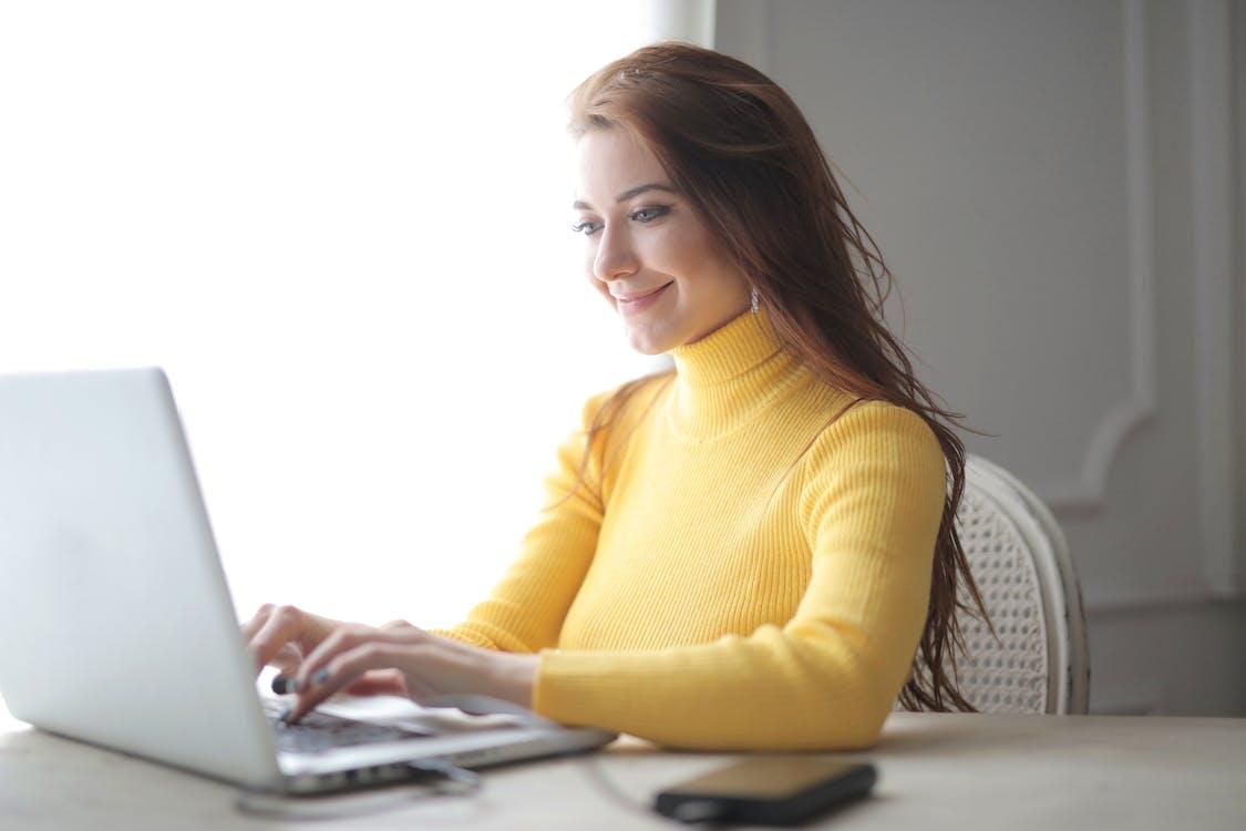 Woman in Yellow Turtleneck Sweater Using Laptop