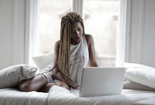 Serious young ethnic lady in sleepwear using laptop while sitting on comfortable bed with pillows near window in light modern apartment