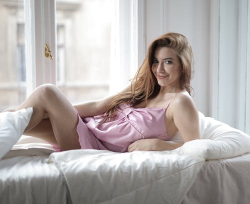 Woman in Pink Spaghetti Strap Dress Ling down on Bed