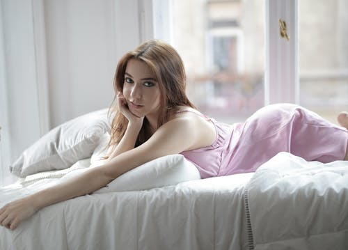 Woman in Pink Dress Lying on Bed