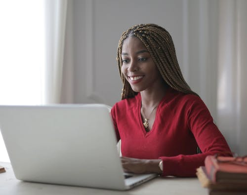 Woman In Red Long Sleeve Shirt Using A Laptop