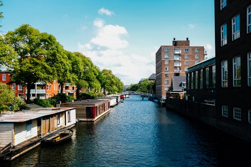 Picturesque channel in Amsterdam with traditional houseboats near modern buildings in city outskirts against blue sky