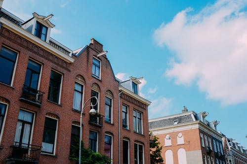 Low angle brick facade of old residential building with balconies and tile roof against blue sky on sunny day