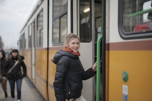 Cheerful young woman in warm outerwear before getting in public transport