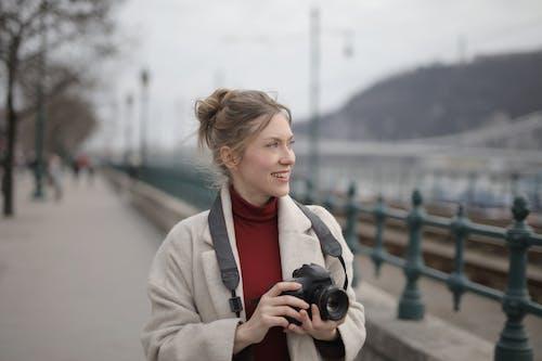 Woman Wearing A Coat Holding Black Dslr Camera