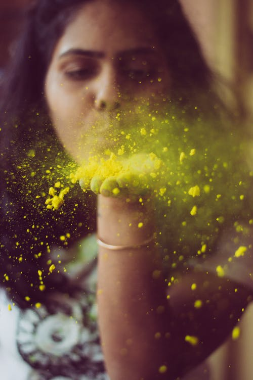 Mujer Soplando Polvo Amarillo