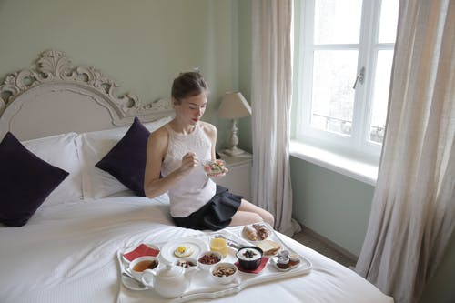 Young attractive woman having breakfast on bed