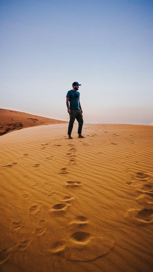 Анонимный мужчина наслаждается видами пустыни, стоя на песчаных дюнах