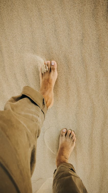 From above of crop anonymous barefooted male traveler walking on sandy terrain in desert