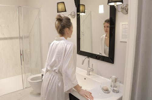 Woman In White Robe Looking At The Mirror