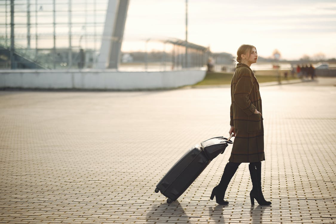 Side view of full length young female traveler in trendy plaid brown coat and high boots with suitcase walking on pavement near modern building on city street in morning