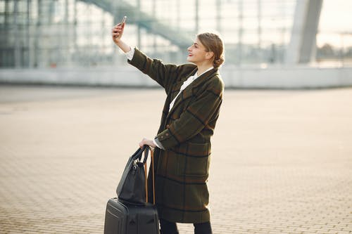 Stylish young woman with luggage taking selfie outside modern glass building