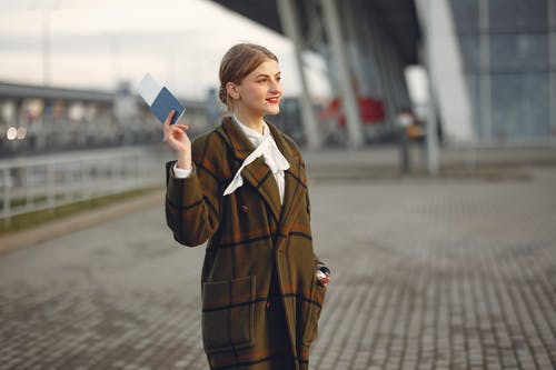 Cheerful female passenger wearing trendy plaid coat taking passport and ticket in raised hand while standing on pavement near modern building of airport outside and looking away with smile