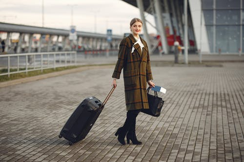 Full body young female passenger in trendy plaid coat with suitcase strolling on pavement near modern building of ariport terminal taking bag and documents