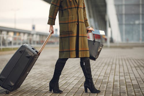 Woman Wearing A Coat Holding Black Luggage Bag