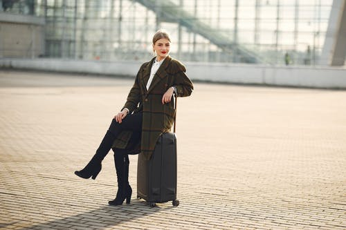 Confident stylish woman sitting on suitcase in front of contemporary glass building on urban street