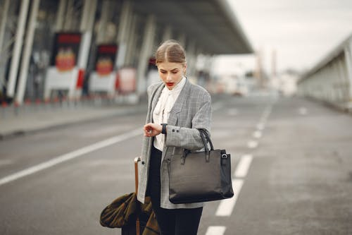 Worried young businesswoman with suitcase hurrying on flight on urban background