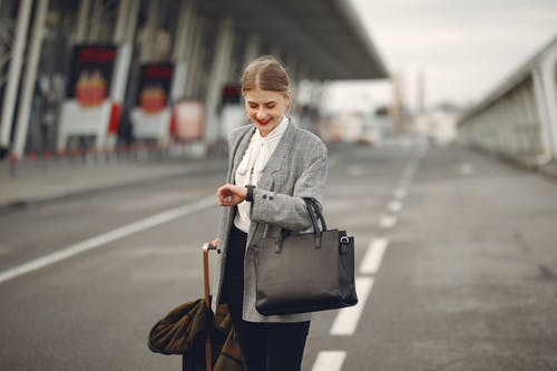 Positive young businesswoman with suitcase hurrying on flight on urban background