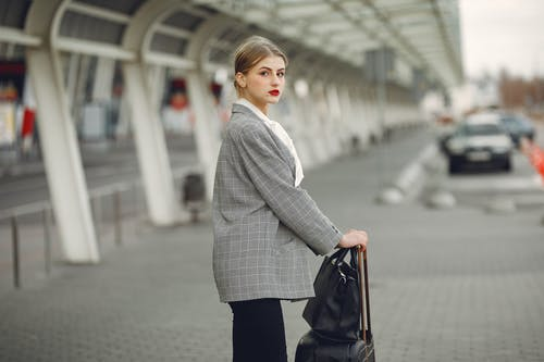Stylish young woman with suitcase near car parking in airport