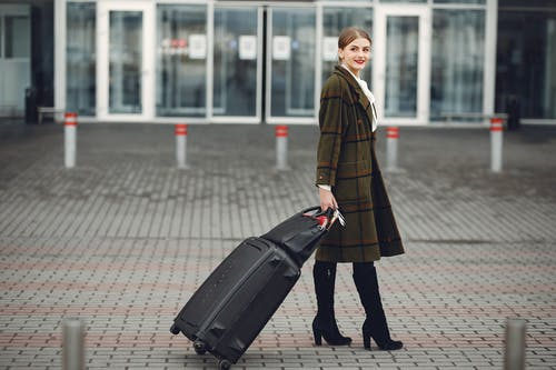 Stylish young woman walking with luggage near airport terminal