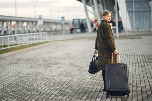 Back view of trendy businesswoman carrying baggage before flight near airport building
