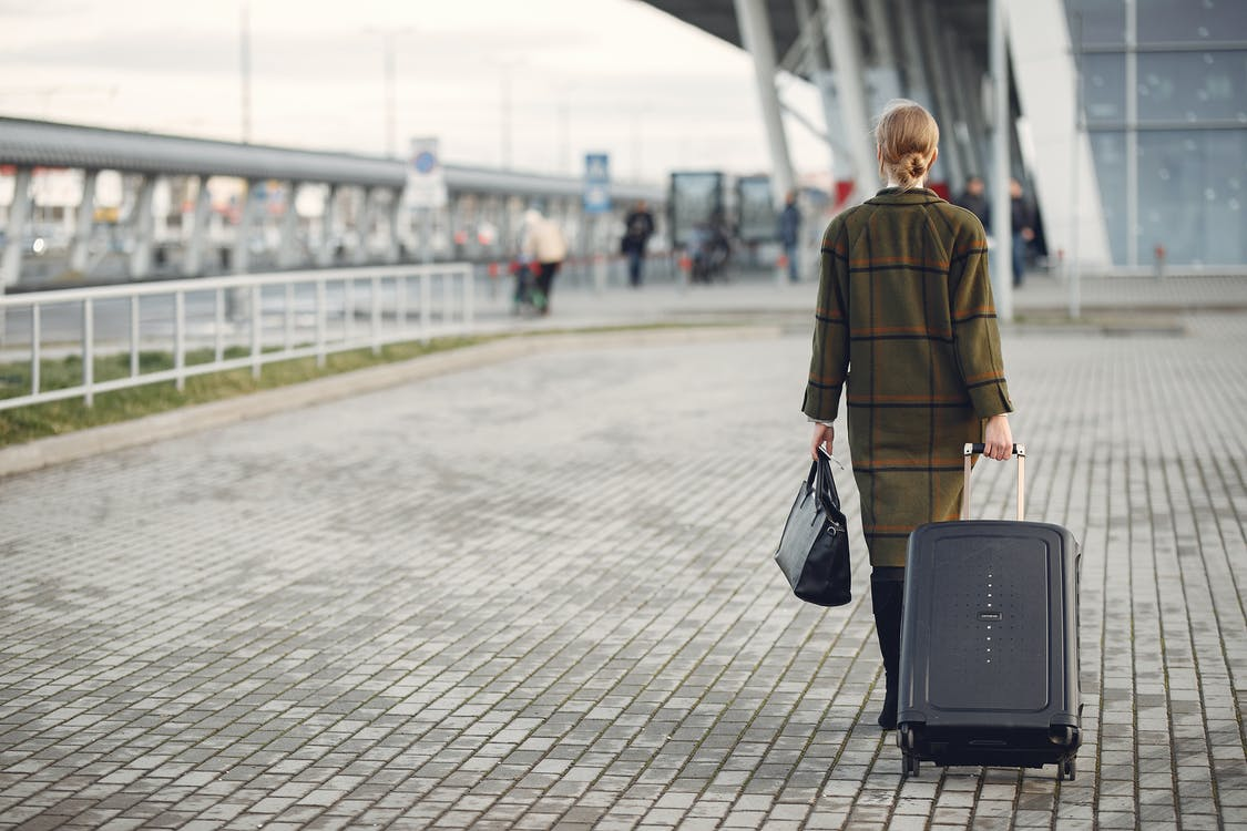 Unrecognizable woman with suitcase walking near airport terminal