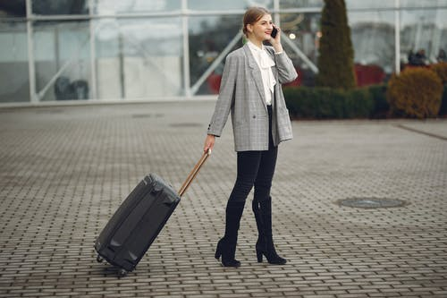 Trendy woman walking with baggage and talking on smartphone near airport