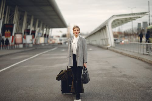 Happy female traveler walking on airport street with luggage