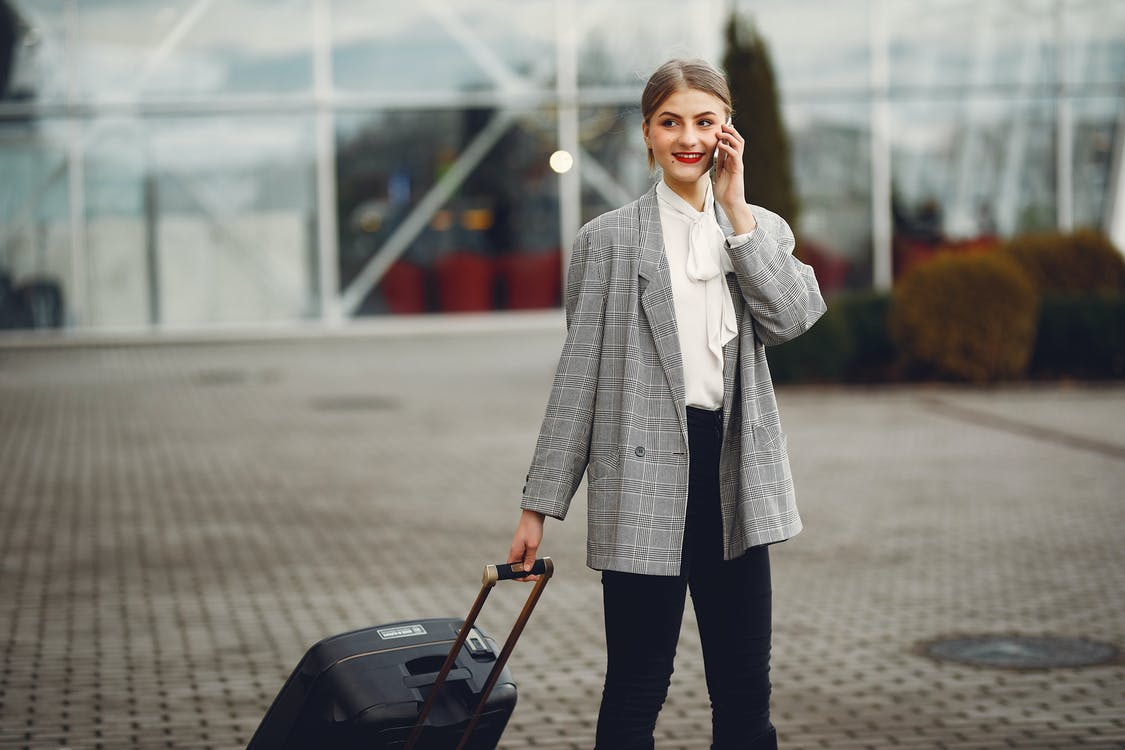Stylish businesswoman speaking on smartphone while standing with luggage near airport