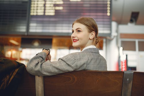Side view of positive female manager waiting for flight on wooden seat in airport