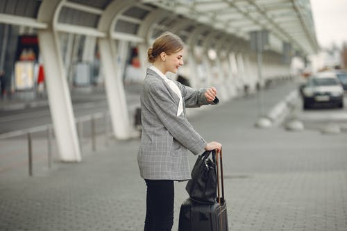 Cheerful female manager checking time on wristwatch standing with bags near bus station