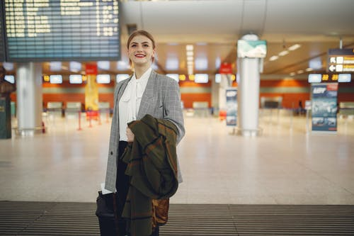 Happy young woman standing with baggage near departure board in airport