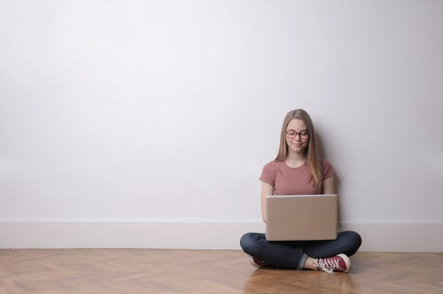 Woman in Pink Crew-neck Top and Jeans Sitting Down on the Floor Using Laptop