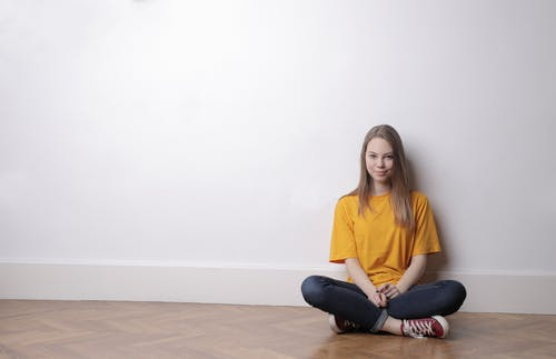 Woman in Yellow Crew-neck T-shirt and Black Pants Sitting on Floor
