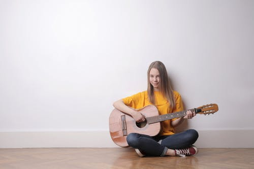 Woman in Yellow Crew-neck T-shirt and Black Pants Playing  Acoustic Guitar