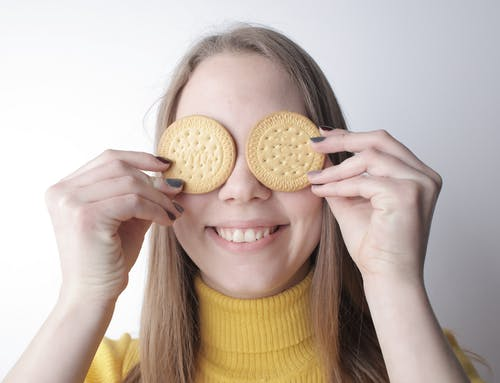 Cheerful woman with tasty cookies in front of eyes