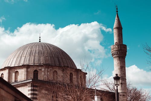 Ancient mosque against cloudy sky