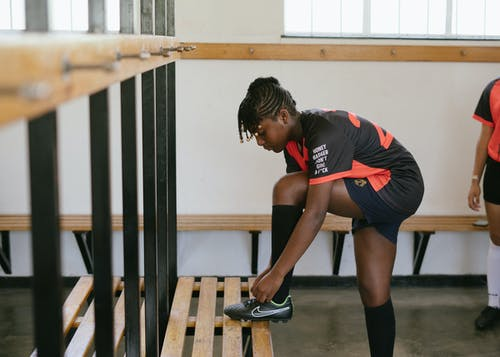 Sporty woman tying shoelaces in dressing room