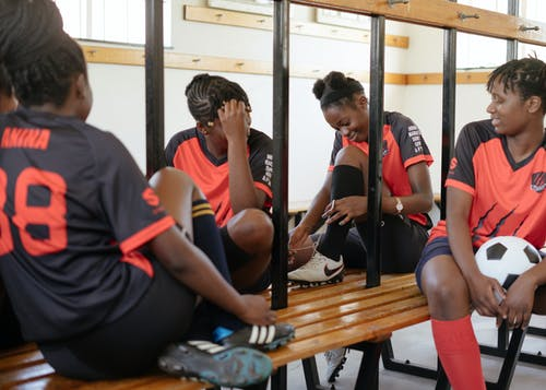 African American athletes resting on bench in locker room