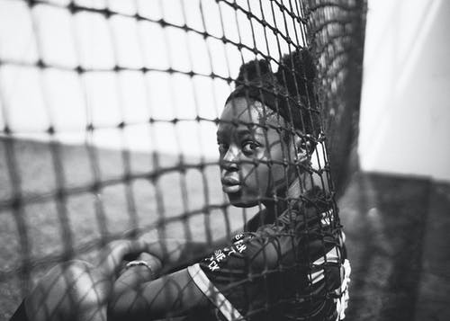 Young woman looking through football goals net