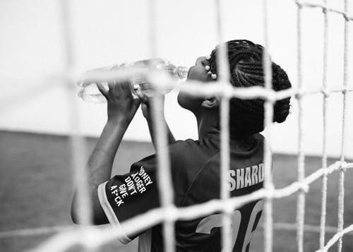 Black and white back view of young female goalkeeper drinking water from plastic bottle