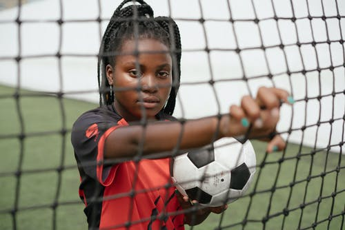 Young woman soccer player with ball in football goals net