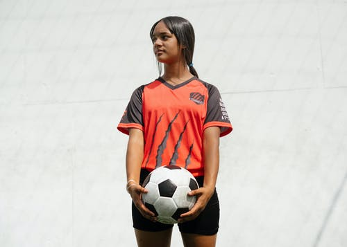 Woman In Red And Black Jersey Shirt Holding Soccer Ball