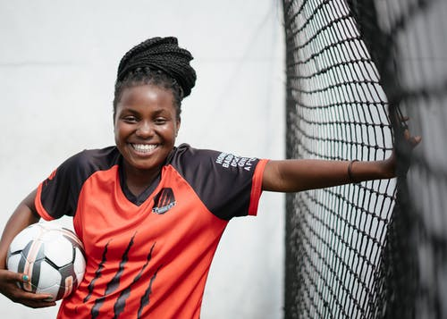 Young happy black woman football player with ball in hand