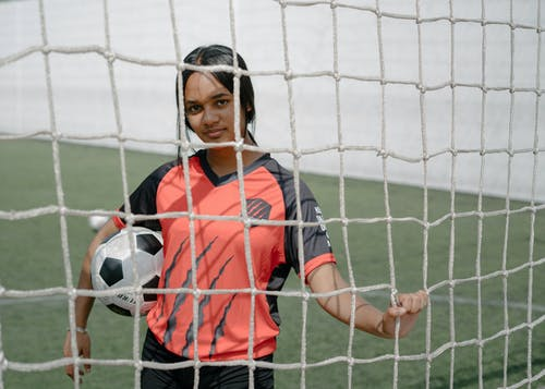 Young ethnic woman soccer player looking over wire fence