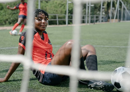 African American woman soccer player laying on football field