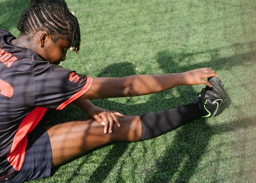 African American football player woman warming up
