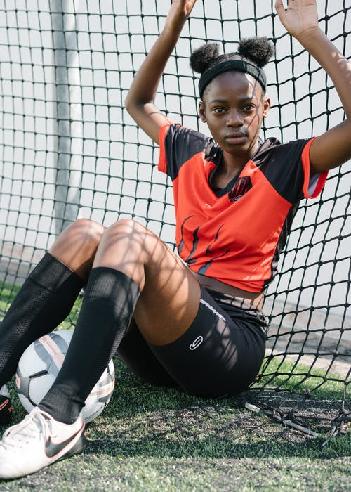 Woman in Red Nike Tank Top and Black Pants Sitting on Soccer Goal Net