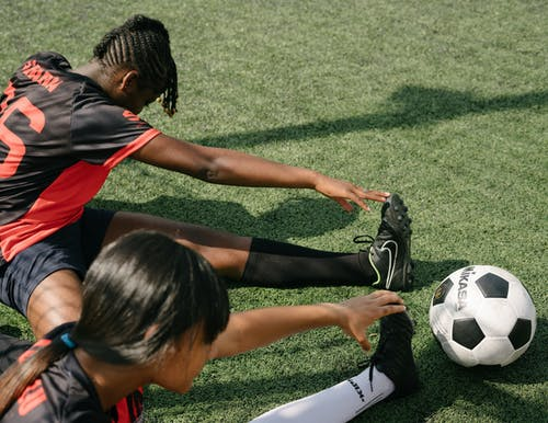 Female football players stretching in training