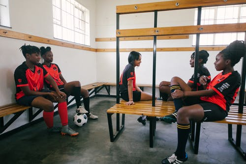 Female football team chatting in changing room